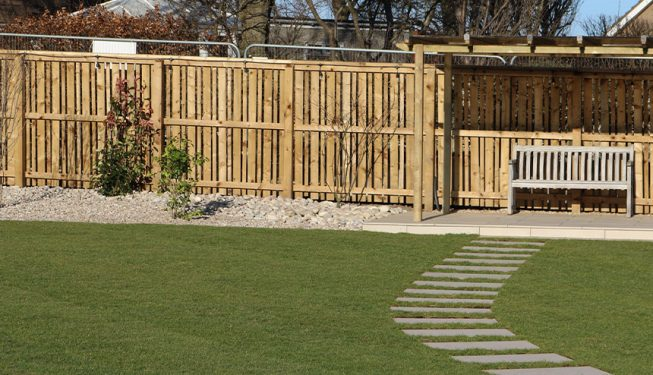Marble Effect Slabs leading up to Wooden Bench in Spacious Garden