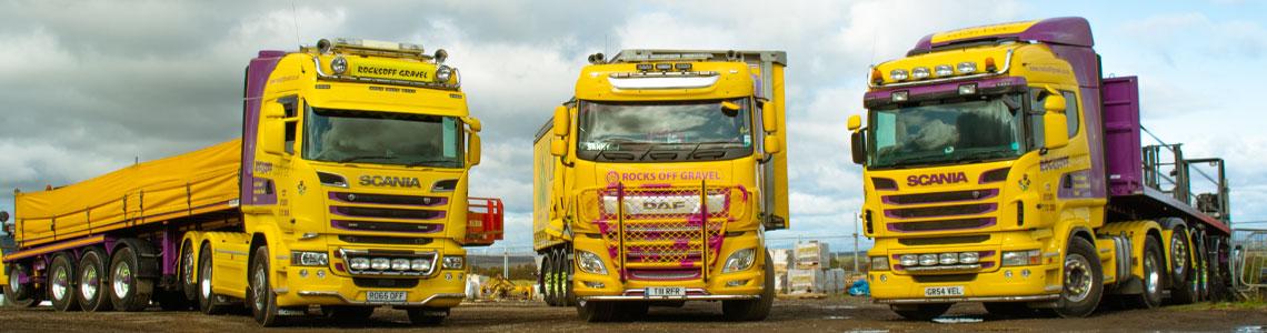 Three yellow and purple Scania Trucks